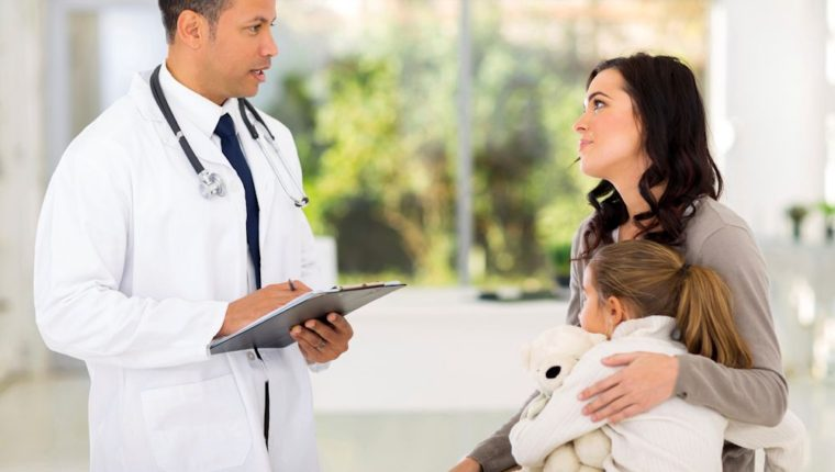 friendly male paediatrician consulting young girl and mother in hospital